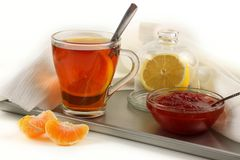 Todavía vida con una taza de té, de limón y de atasco imagen de archivo