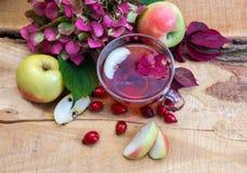 Todavía vida con una taza de té a partir del otoño de los escaramujos y de las manzanas Fotos de archivo libres de regalías