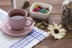 Todavía vida con una taza de té, un platillo, una cuchara, y un cuenco de caramelos Imagenes de archivo
