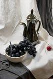 Todavía vida con una tetera negra, manojo de uvas y cereza madura Fotografía de archivo