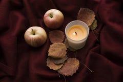 Todavía vida con una vela, una manzana y hojas Imagen de archivo libre de regalías