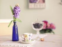 Todavía vida con wal color de rosa y azul de la taza de té de las flores del jacinto del florero Imagen de archivo