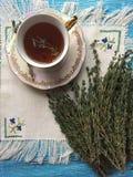 Todavía vida:  de Ñ para arriba del té negro con tomillo y el manojo fresco del tomillo Imágenes de archivo libres de regalías
