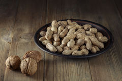 Todavía vida de cacahuetes en un plato y nueces de la loza de barro Fotos de archivo