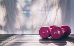 Todavía vida de dos pesas de gimnasia rosadas en de madera por la mañana o la víspera Fotos de archivo