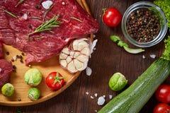 Todavía vida de la carne cruda de la carne de vaca con las verduras en la placa de madera sobre el fondo del vintage, visión supe Imagenes de archivo