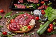 Todavía vida de la carne cruda de la carne de vaca con las verduras en la placa de madera sobre el fondo del vintage, visión supe Imagen de archivo libre de regalías