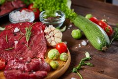 Todavía vida de la carne cruda de la carne de vaca con las verduras en la placa de madera sobre el fondo del vintage, visión supe Imágenes de archivo libres de regalías