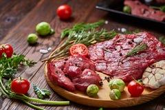 Todavía vida de la carne cruda de la carne de vaca con las verduras en la placa de madera sobre el fondo del vintage, visión supe Imagen de archivo
