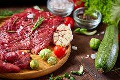 Todavía vida de la carne cruda de la carne de vaca con las verduras en la placa de madera sobre el fondo del vintage, visión supe Fotos de archivo libres de regalías