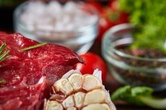 Todavía vida de la carne cruda de la carne de vaca con las verduras en la placa de madera sobre el fondo del vintage, visión supe Foto de archivo libre de regalías