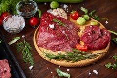 Todavía vida de la carne cruda de la carne de vaca con las verduras en la placa de madera sobre el fondo del vintage, visión supe Fotos de archivo