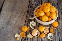 Todavía vida de la fruta anaranjada en cuenco en viejo fondo de madera Imágenes de archivo libres de regalías