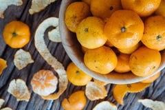 Todavía vida de la fruta anaranjada en cuenco en viejo fondo de madera Imagen de archivo libre de regalías