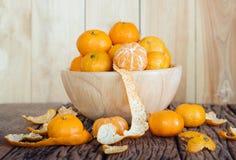 Todavía vida de la fruta anaranjada en cuenco en viejo fondo de madera Fotografía de archivo libre de regalías