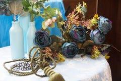 Todavía vida de las botellas artificiales del flor y de cristal Fotos de archivo libres de regalías