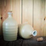 Todavía vida de las botellas del motivo con la luz en el fondo de madera Imagen de archivo libre de regalías