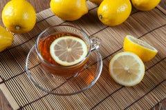 Todavía vida de limones frescos en una servilleta de bambú con la taza de té Imágenes de archivo libres de regalías