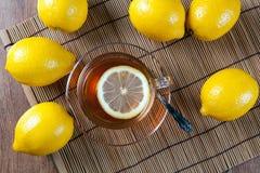 Todavía vida de limones frescos en una servilleta de bambú con la taza de té Imagen de archivo