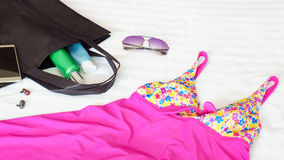Todavía vida de los accesorios del verano en la cama blanca Imágenes de archivo libres de regalías