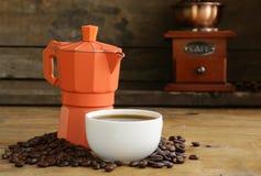 Todavía vida de los granos de café y del fabricante de café, taza de café express Foto de archivo