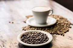 Todavía vida de los granos de la taza y de café del capuchino Foto de archivo