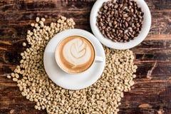 Todavía vida de los granos de la taza y de café del capuchino Foto de archivo libre de regalías