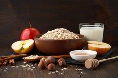 Todavía vida de los ingredientes para el desayuno sano: la avena rodada forma escamas, ordeña, manzana, miel, avellana, canela Imagen de archivo
