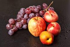 Todavía vida de melocotones de manzanas y de uvas Imagen de archivo