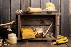 Todavía vida de productos apiculturales con la cera, las velas y la miel Fotografía de archivo