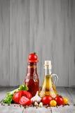 Todavía vida de tomates, de la salsa de tomate y del aceite de oliva frescos en los tableros de madera grises Imagenes de archivo