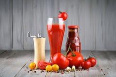 Todavía vida de tomates, del ajo, del jugo de tomate y de la salsa de tomate en los tableros de madera Fotografía de archivo libre de regalías