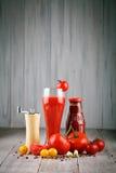 Todavía vida de tomates, del ajo, del jugo de tomate y de la salsa de tomate en los tableros de madera Foto de archivo