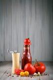 Todavía vida de tomates, del ajo y de la salsa en los tableros de madera grises Foto de archivo libre de regalías