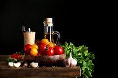 Todavía vida de tomates, del ajo y del aceite de oliva en los tableros de madera En un fondo negro Foto de archivo
