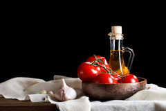 Todavía vida de tomates, del ajo y del aceite de oliva en los tableros de madera En un fondo negro Fotos de archivo