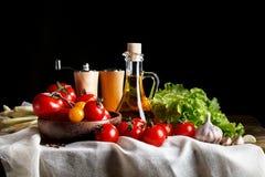 Todavía vida de tomates, del ajo y del aceite de oliva en los tableros de madera En un fondo negro Imagen de archivo