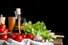 Todavía vida de tomates, del ajo y del aceite de oliva en los tableros de madera En un fondo negro Fotos de archivo libres de regalías