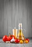 Todavía vida de tomates, del ajo y del aceite de oliva en los tableros de madera grises Imagenes de archivo