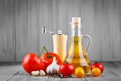 Todavía vida de tomates, del ajo y del aceite de oliva en los tableros de madera grises Fotos de archivo libres de regalías