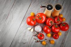 Todavía vida de tomates, del ajo y del aceite de oliva en los tableros de madera grises Fotografía de archivo