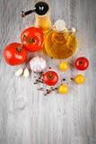 Todavía vida de tomates, del ajo y del aceite de oliva en los tableros de madera grises Imágenes de archivo libres de regalías