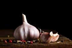 Todavía vida de tomates, del ajo y del perejil en los tableros de madera En un fondo negro Foto de archivo