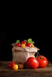 Todavía vida de tomates, del ajo y del perejil en los tableros de madera En un fondo negro Foto de archivo libre de regalías