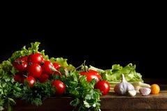 Todavía vida de tomates, del ajo y del perejil en los tableros de madera En un fondo negro Imagenes de archivo