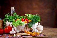 Todavía vida de tomates, del ajo y del perejil frescos en los tableros de madera Imagenes de archivo