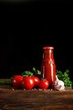 Todavía vida de tomates y de la salsa de tomate frescos en los tableros de madera En un fondo negro Imagen de archivo