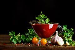 Todavía vida de tomates y de la salsa de tomate frescos en los tableros de madera En un fondo negro Imagenes de archivo