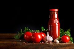 Todavía vida de tomates y de la salsa de tomate frescos en los tableros de madera En un fondo negro Foto de archivo libre de regalías