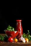 Todavía vida de tomates y de la salsa de tomate frescos en los tableros de madera En un fondo negro Fotos de archivo